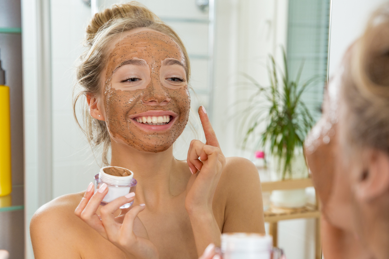 Young beautiful girl applying facial scrub mask on skin.